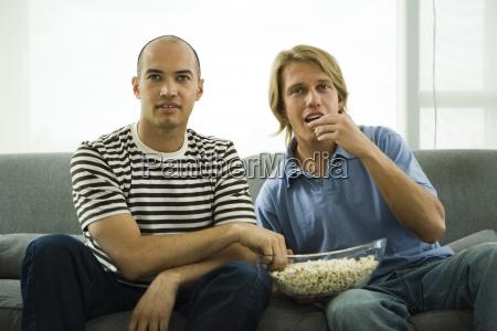 two men sitting on sofa eating