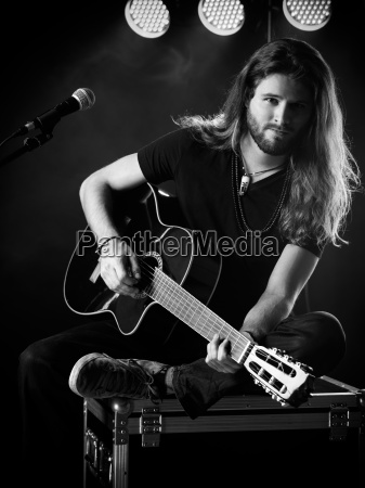 man playing acoustic guitar on stage