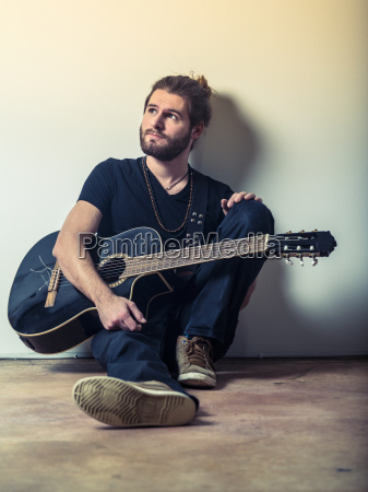 young man sitting and holding guitar