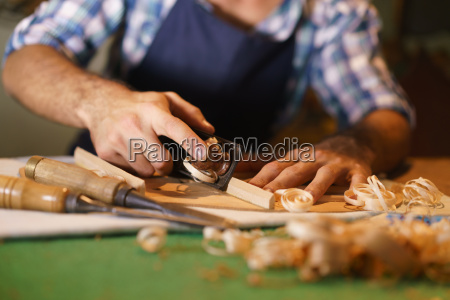 artisan lute maker chiseling stringed instrument