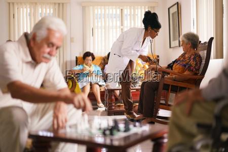 hospice doktor blutdruckmessung mit aelteren frau