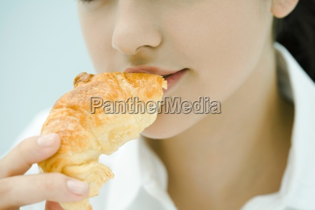 young woman eating croissant close up