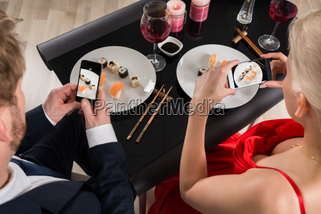 couple making picture of food with