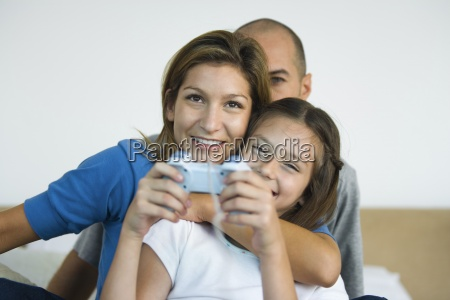 girl playing video game parents watching