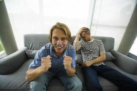 two men sitting on sofa watching
