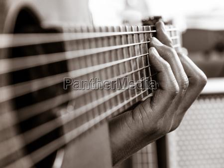 closeup of playing an acoustic guitar