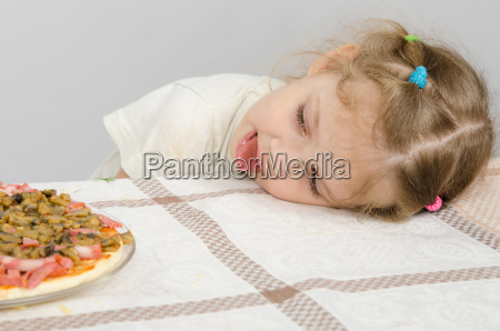 little girl with protruding tongue rested