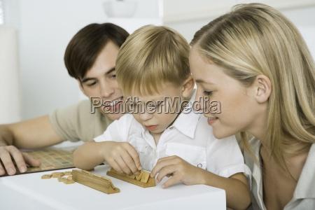 parents watching as little boy arranges