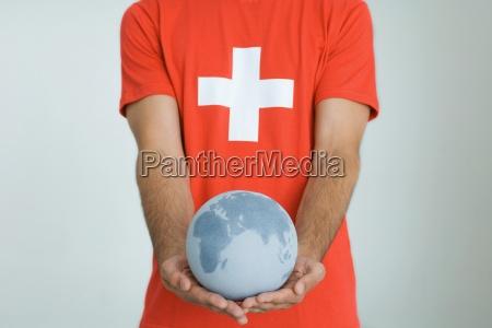 mann traegt schweizer flagge t shirthalten