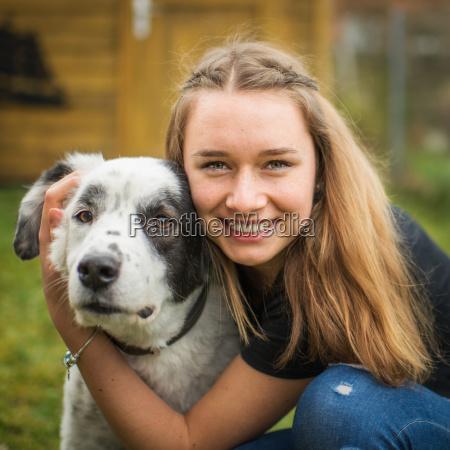 young girl in portrait hugs her
