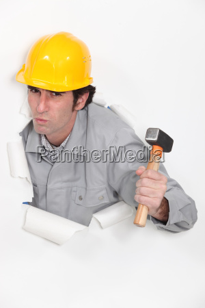 carpenter with hammer against torn paper