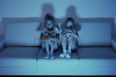 two girls watching tv together on