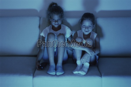 two girls watching tv together at