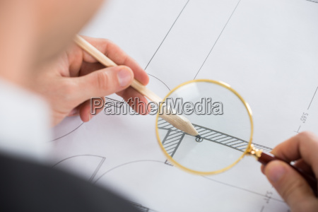 architect working with magnifying glass