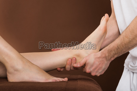 woman receiving foot massage at spa