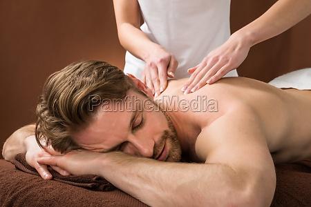 junger mann am spa empfangen rueckenmassage