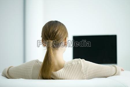 woman watching tv rear view