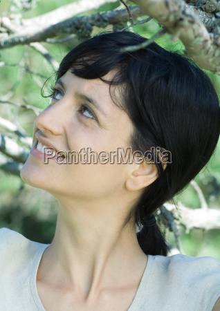 woman standing under branches head and