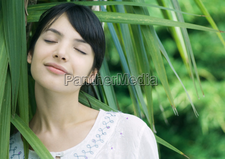 woman standing amongst leaves head and