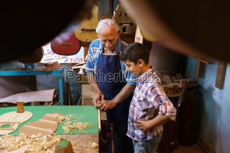old lute maker teaching grandson boy