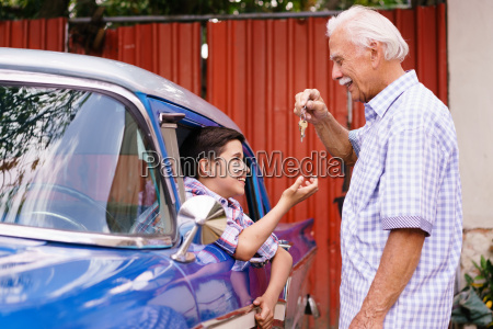 senior man grandfather giving car keys