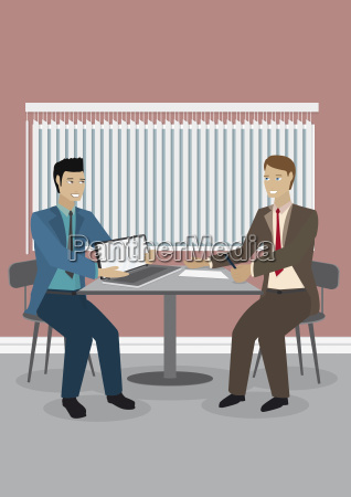 two businessmen with laptop at table