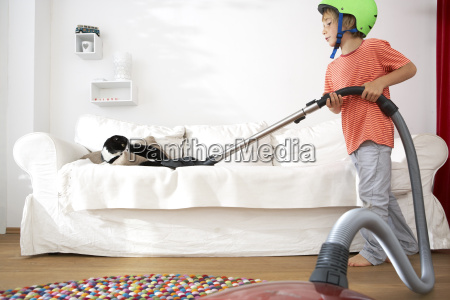 boy in living room hoovering the