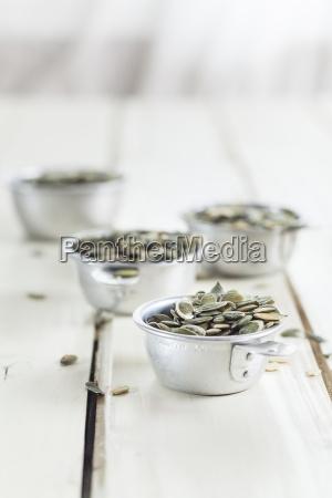 four metal bowls of pumpkin seeds