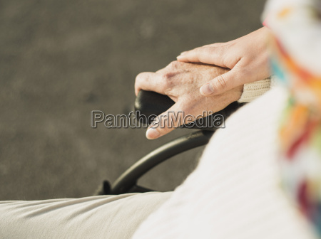 young womans hand on hand of