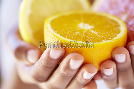 womans hands holding halves of orange