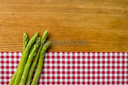 green asparagus on wood background with