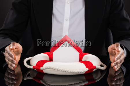 businesspersons hand protecting house with lifebelt