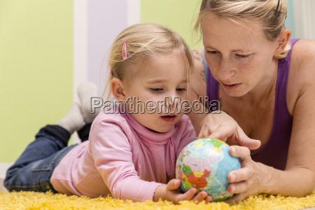 mutter und tochter mit kleinem globus
