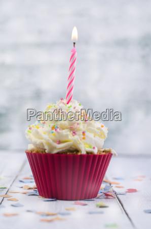 cupcake mit angezuendeter kerze und konfetti