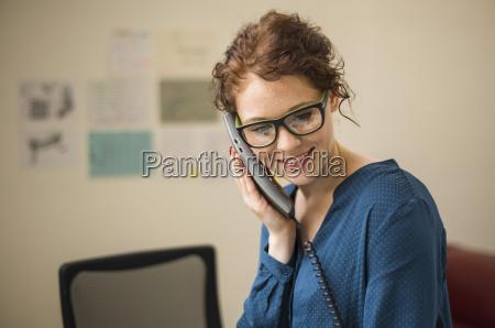 laechelnde junge frau am telefon