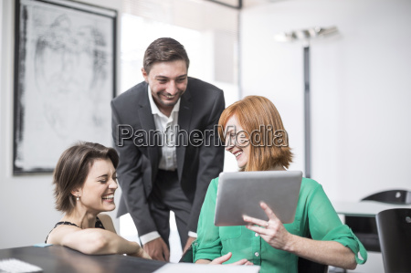 geschaeftsfrau zeigt digitale tablet zu lachen