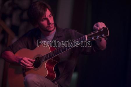 man tuning an acoustic guitar