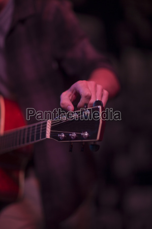 mans hand tuning an acoustic guitar