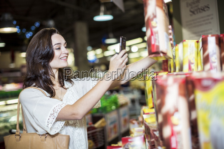 frau im supermarkt scannt preise mit