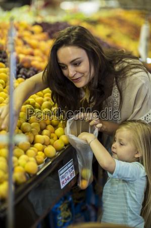 mutter und tochter im supermarkt einkaufen