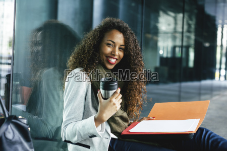 smiling young businesswoman with coffee to