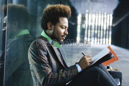 young businessman sitting outdoors writing in