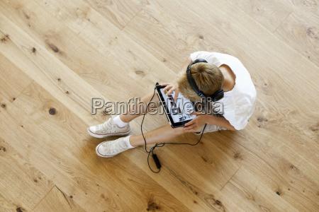 junge sitzt auf holzboden mit digitalen