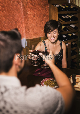 couple clinking red wine glasses in