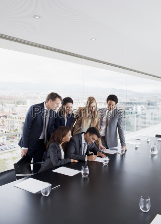 business people watching businessman sign contract