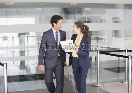 smiling businessman and businesswoman with file