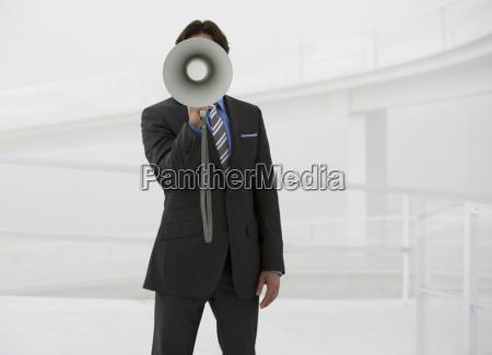 portrait der geschaeftsmann mit megafon