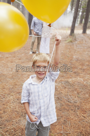 portrait of smiling boy holding balloons