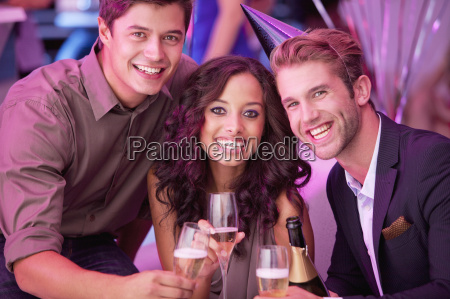 portrait of smiling friends drinking champagne