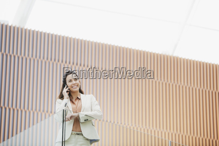 smiling businesswoman talking on cell phone